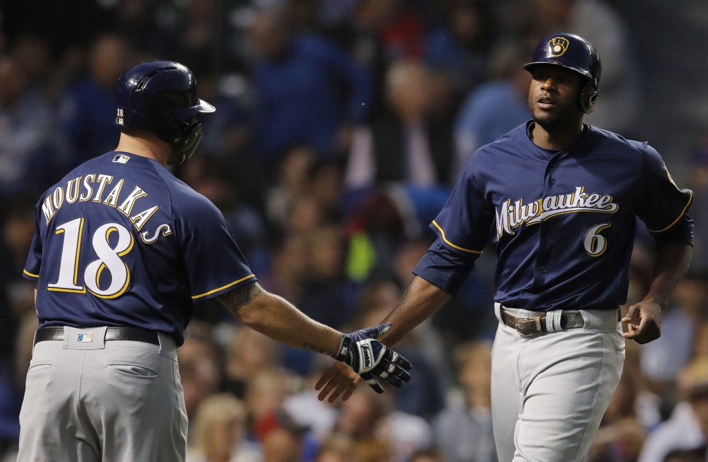 Milwaukee Brewers' Lorenzo Cain, right, celebrates scoring a run against the Chicago Cubs with teammate Mike Moustakas during the first inning of a ba