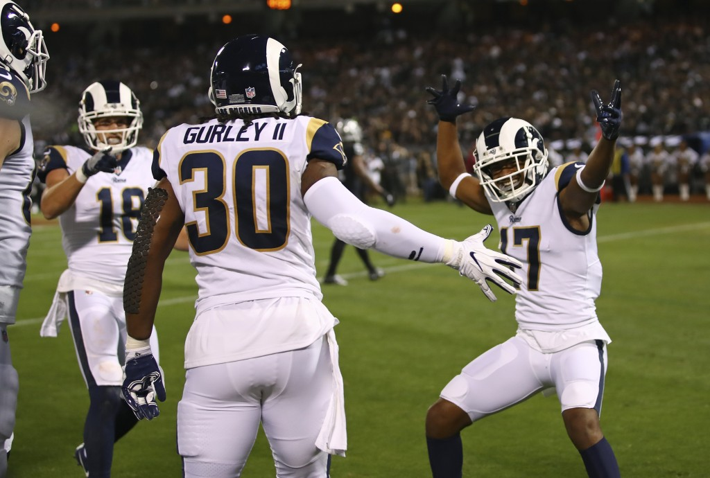 Los Angeles Rams running back Todd Gurley is greeted by teammates Cooper Kupp (18) and Robert Woods (17) after scoring a touchdown during the first ha...