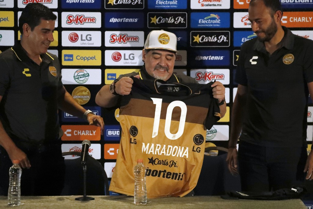 Former soccer great Diego Maradona shows his team jersey during a press conference where he was presented as the new manager of the Dorados of Sinaloa