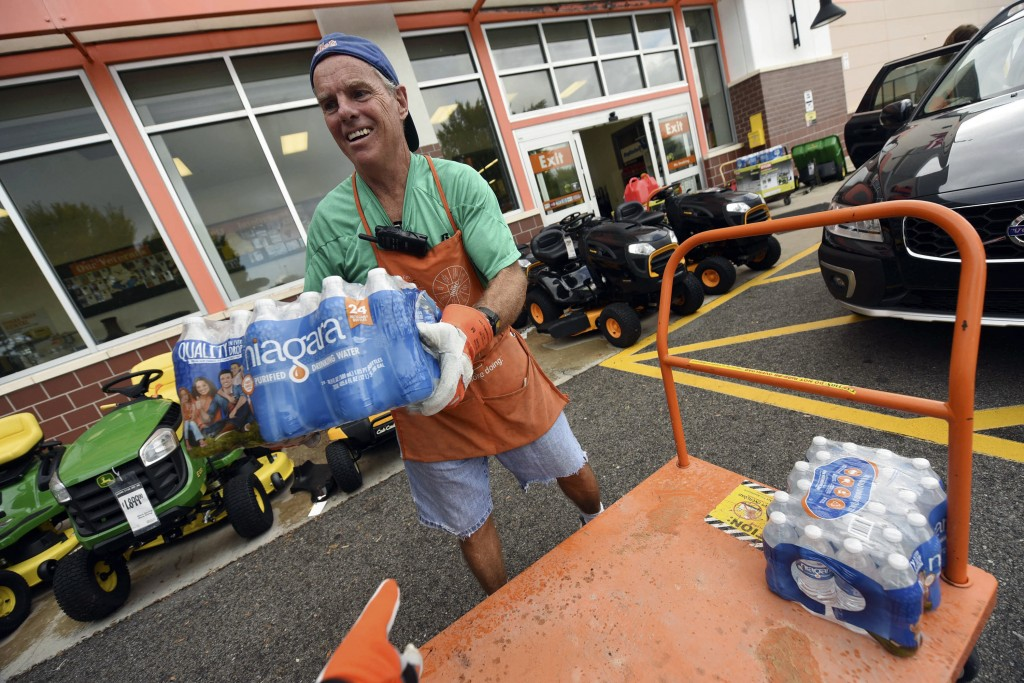 Chris Rayner helps customers load their cars as they buy supplies at The Home Depot on Monday, Sept. 10, 2018, in Wilmington, N.C. Hurricane Florence