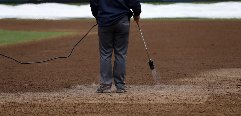 A grounds crew member heats the infield of Citizens Bank Park before a baseball game between the Philadelphia Phillies and Washington Nationals, Monda