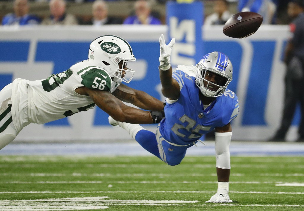 Detroit Lions running back Theo Riddick (25) reaches for the ball as New York Jets linebacker Kevin Pierre-Louis (56) defends in the first half of an
