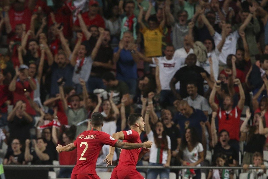 Portugal's Andre Silva, right celebrates after scoring the opening goal during the UEFA Nations League soccer match between Portugal and Italy at the