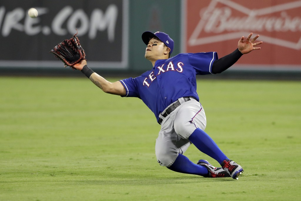 Texas Rangers right fielder Shin-Soo Choo makes a sliding catch on a fly ball from Los Angeles Angels' Jose Briceno during the fourth inning of a base