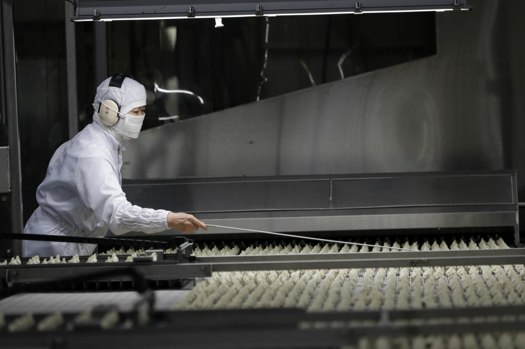In this July 18, 2018, photo, a worker inspects dumplings on a conveyor belt to pick out a defective product at an automated factory of CJ CheilJedang