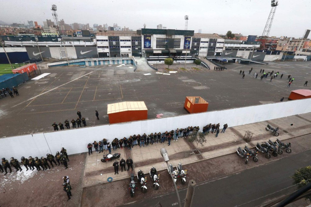 In this photo provided by the Andina government news agency, police stand guard outside the parking lot of the Alianza Lima soccer club stadium after