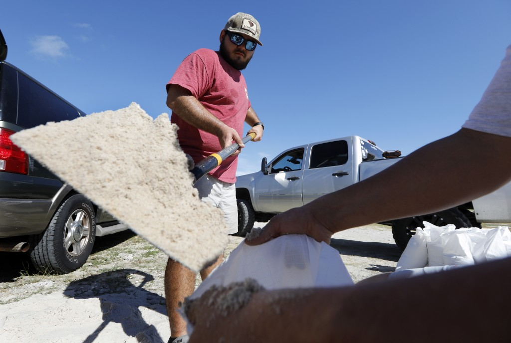 Walker Townsend, at left, from the Isle of Palms, S.C., fills a sand bag while Dalton Trout, at right, holds the bag at the Isle of Palms municipal lo