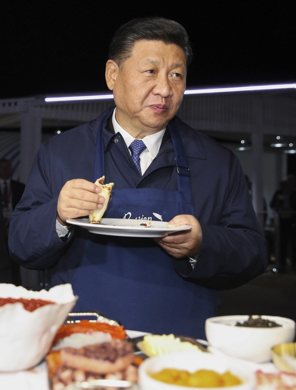 Chinese President Xi Jinping tastes food, as he and Russian President Vladimir Putin visit an exhibition during the Eastern Economic Forum in Vladivos