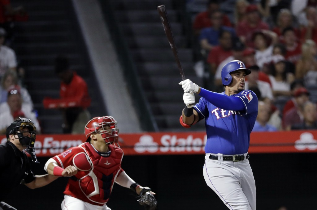 Texas Rangers' Ronald Guzman, right, follows through on his two-run home run against the Los Angeles Angels during the second inning of a baseball gam