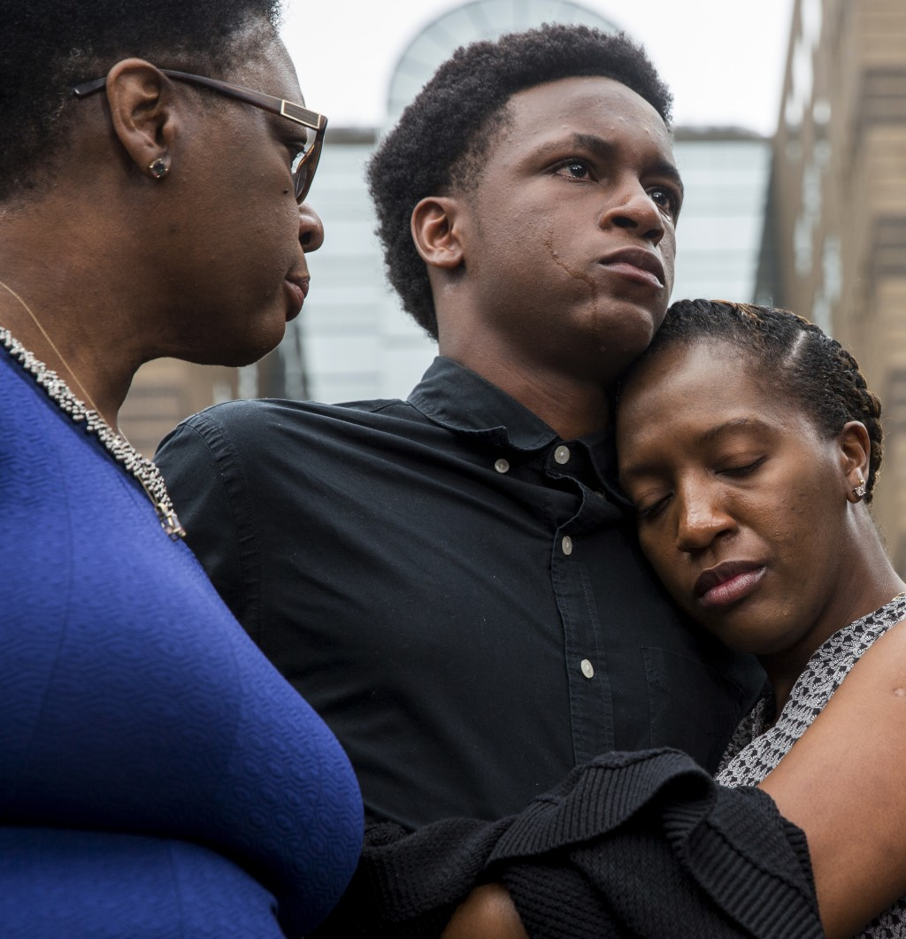 Brandt Jean, brother of Botham Jean, is comforted by his sister, Allisa Charles-Findley, as their mother, Allison, looks on during a news conference o