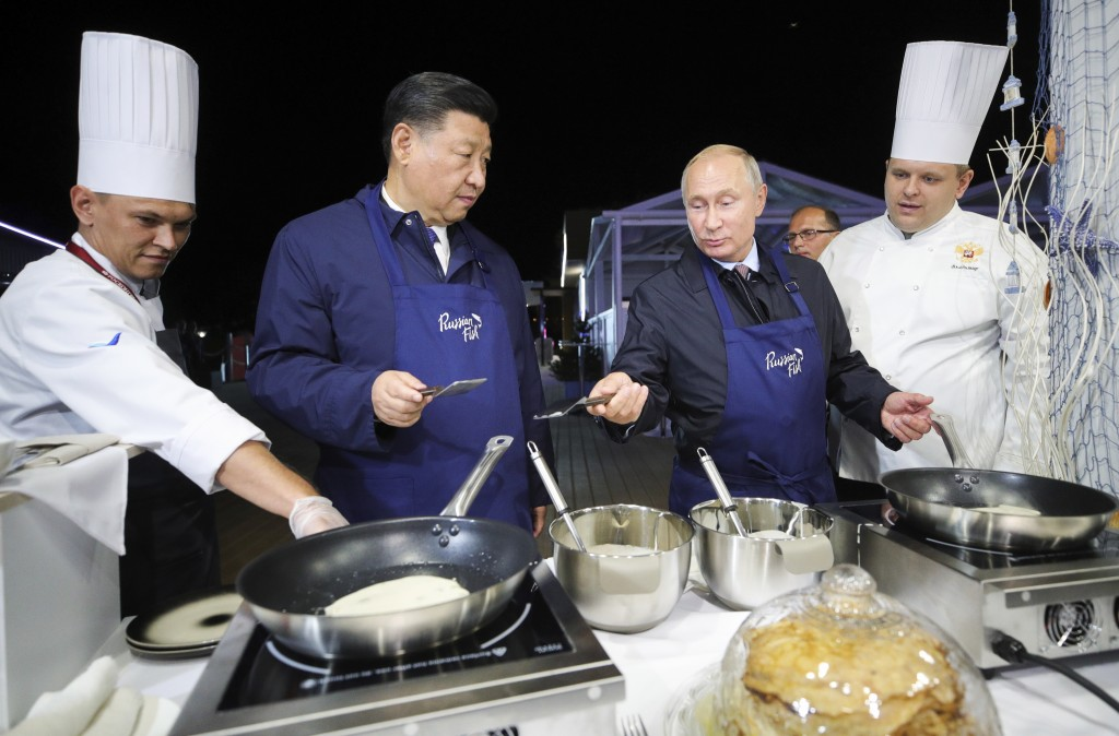 Chinese President Xi Jinping, second left, and Russian President Vladimir Putin, prepare food as they visit an exhibition during the Eastern Economic