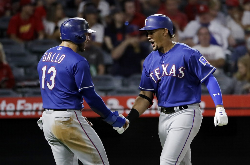 Texas Rangers' Ronald Guzman, right, celebrates his two-run home run with teammate Joey Gallo (13) during the second inning of a baseball game against