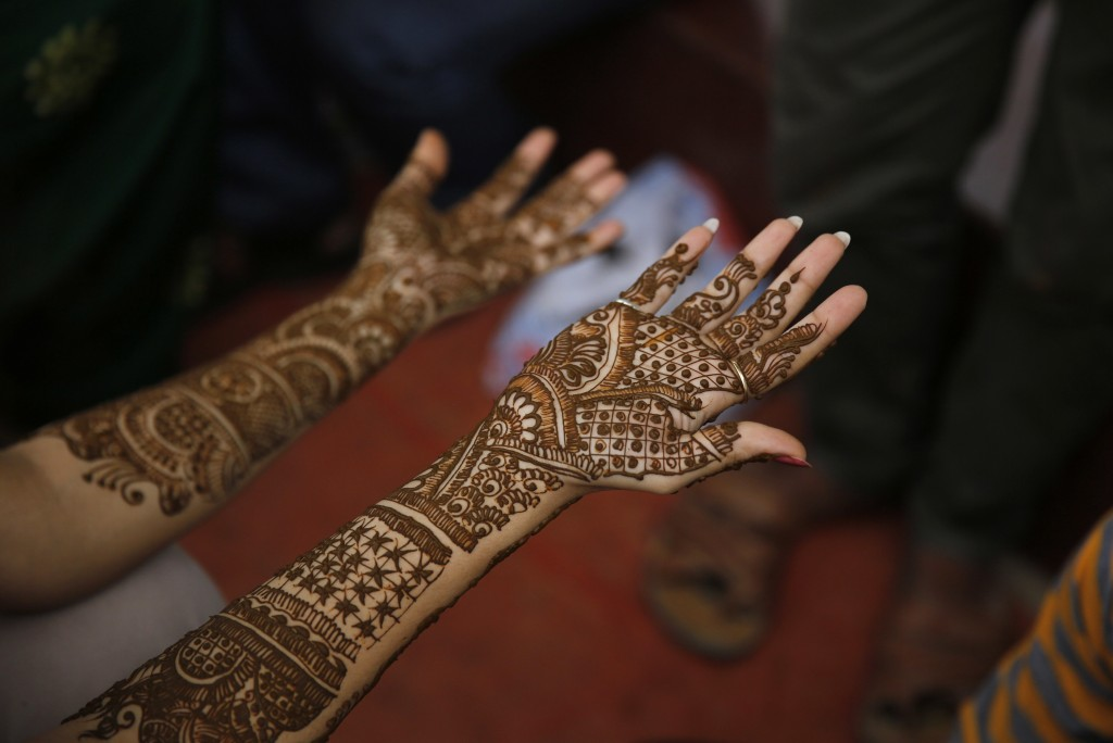 In this Tuesday, Sept. 11, 2018, file photo, a woman waits for her fresh henna covered hands to dry, on the eve of the Hindu festival of Teej, in Alla