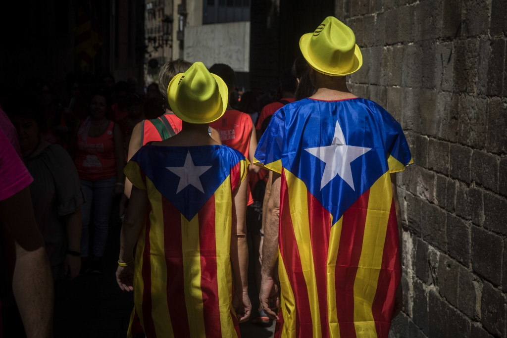 A couple wrapped in Catalan independence flags walk down a street during  Catalan National Day in downtown Barcelona, Spain, Tuesday, Sept. 11, 2018.