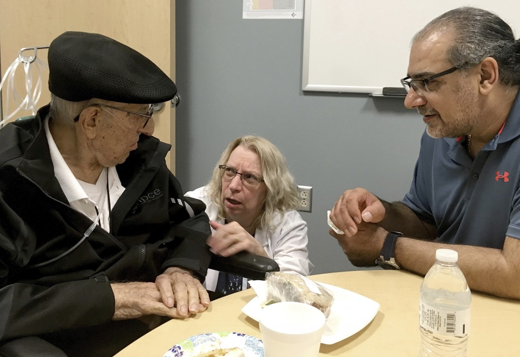 The Rev. John Sabbagh, left, and his son Ebby Sabbagh talk with nurse practitioner Kim O'Riley, Friday, Sept. 7, 2018 in Gilbert, Ariz. Thirty-five ye