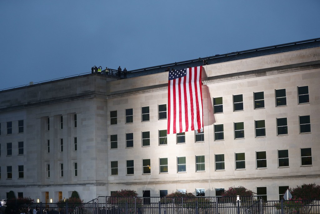 A U.S. flag is unfurled at sunrise on Tuesday, Sept. 11, 2018, at the Pentagon on the 17th anniversary of the Sept. 11, 2001, terrorist attacks. (AP P