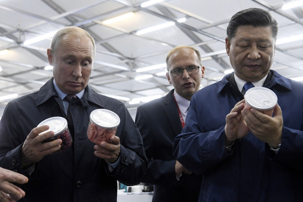 Chinese President Xi Jinping, right, and Russian President Vladimir Putin look at containers of food as they visit an exhibition during the Eastern Ec