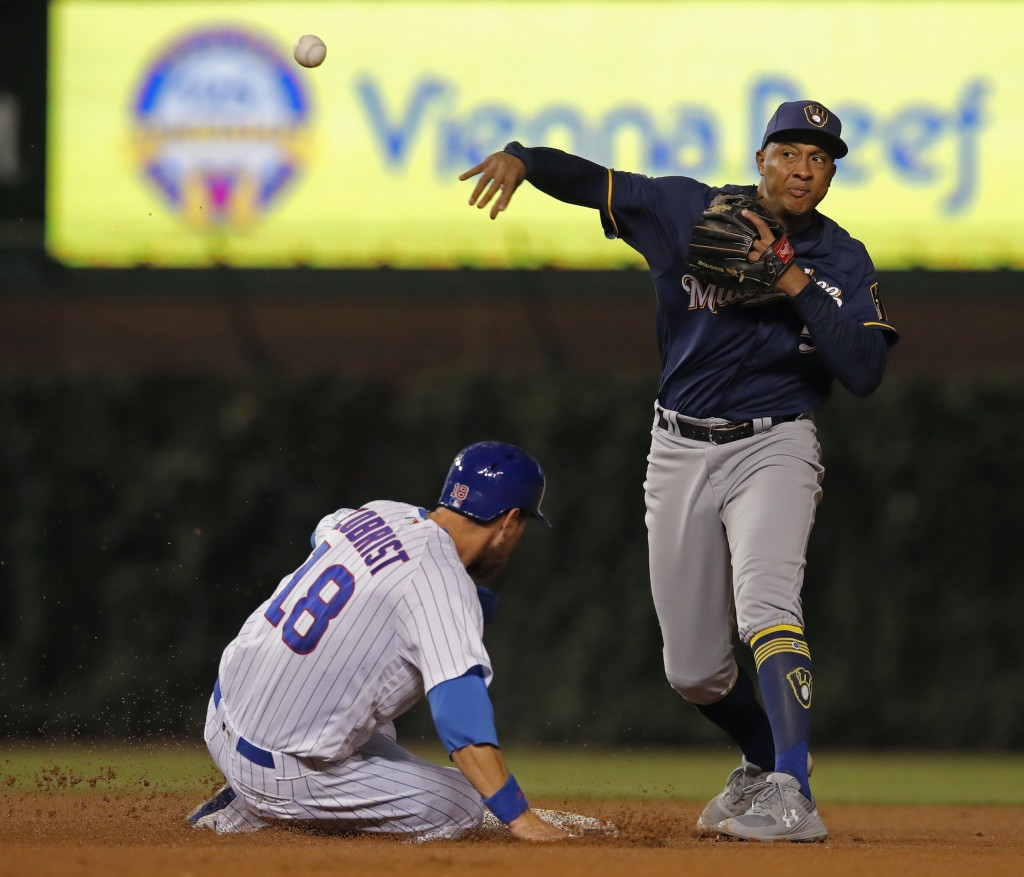 Milwaukee Brewers' Jonathan Schoop, right, makes a throw to first base as Chicago Cubs' Ben Zobrist is out at second base during the fourth inning of