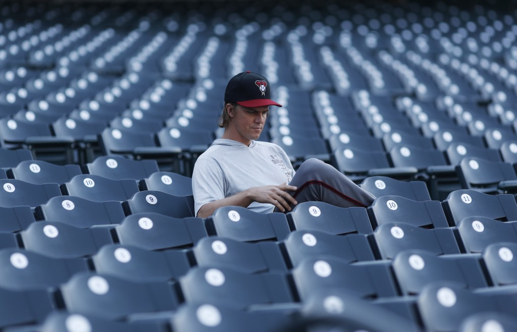 Arizona Diamondbacks starting pitcher Zack Greinke reads in the empty stands before a baseball game against the Colorado Rockies Monday, Sept. 10, 201