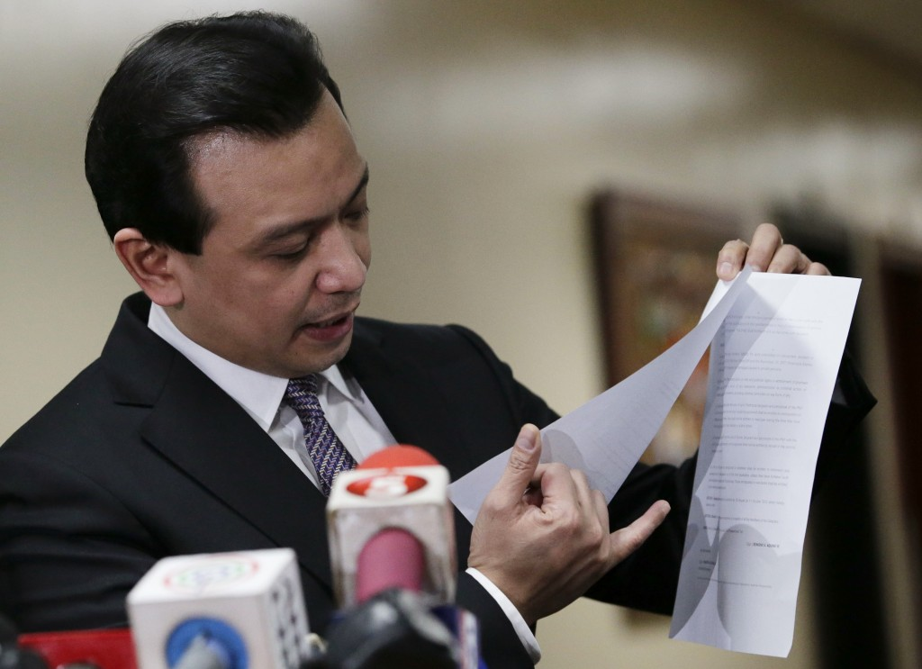Philippine opposition Sen. Antonio Trillanes IV shows to reporters a copy of his amnesty documents outside his office where he remains holed up in the