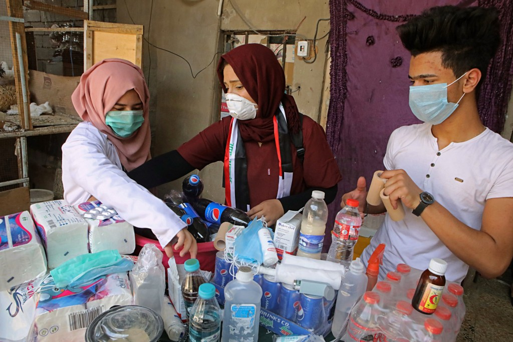 In this Sunday, Sept. 9, 2018 photo, Duhaa Mayaa, center, and her two children, prepare first aid material for injured protesters, in their home in Ba