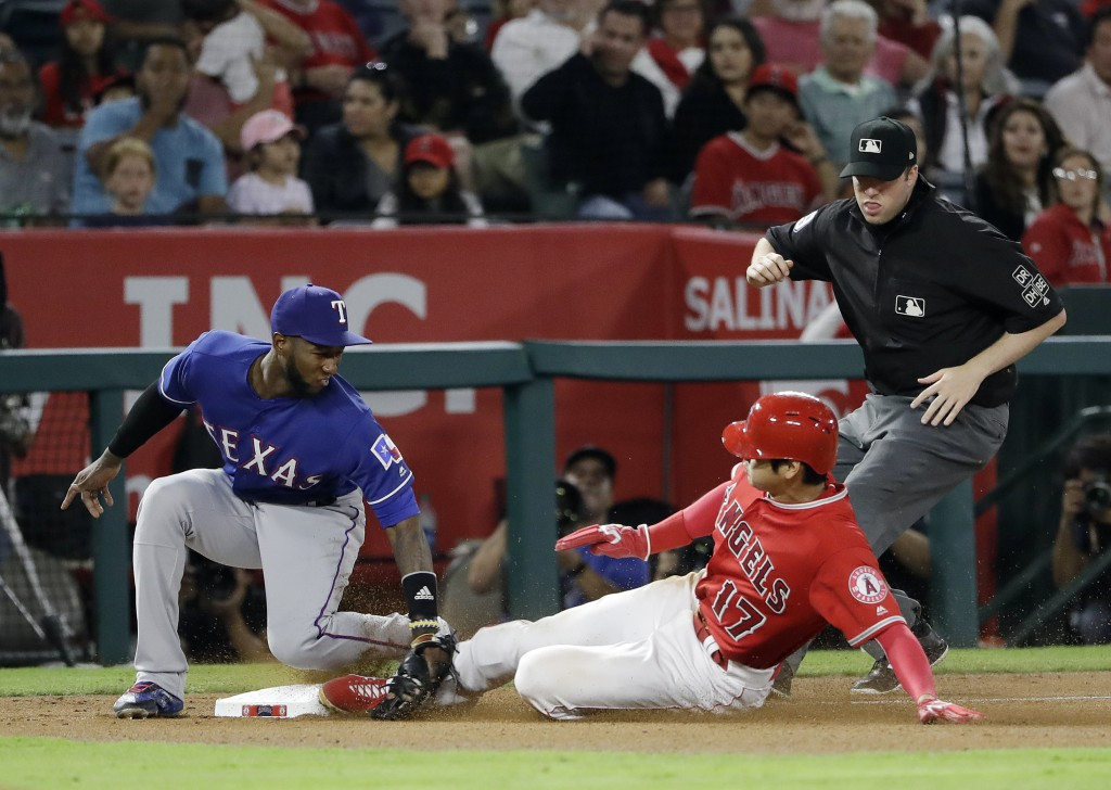 Los Angeles Angels' Shohei Ohtani, right, steals third base before the tag by Texas Rangers third baseman Jurickson Profar during the fourth inning of