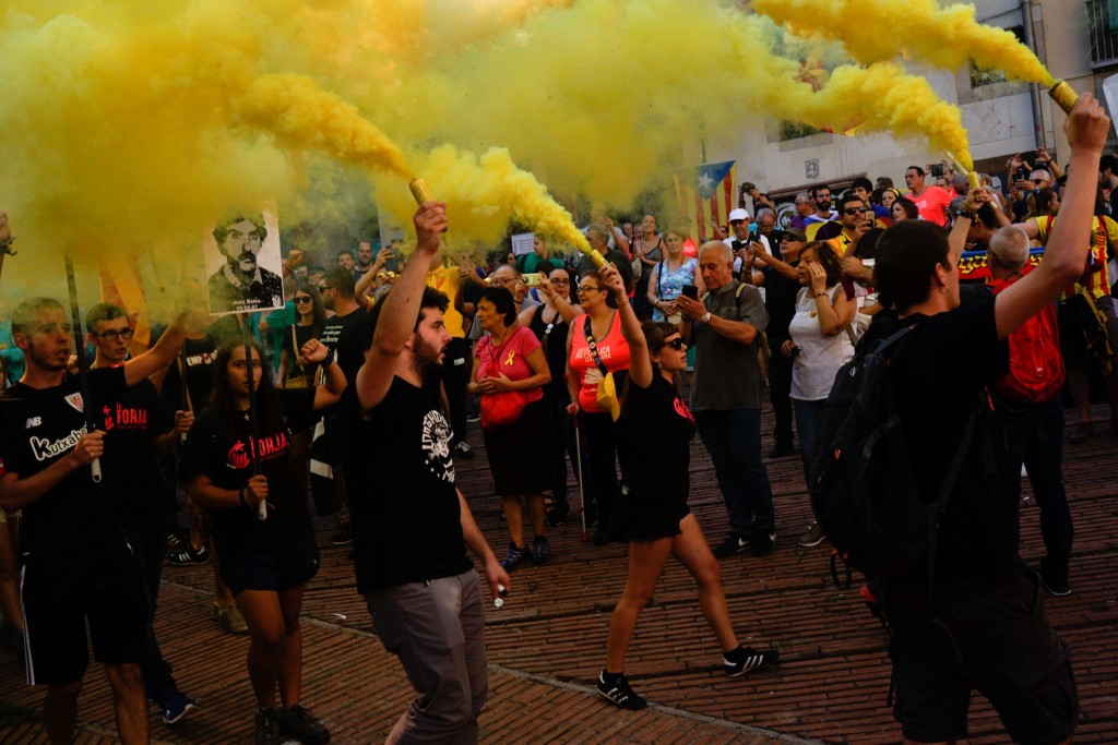 Independence demonstrators, some of them holding flares, march during the Catalan National Day in Barcelona, Spain, Tuesday, Sept. 11, 2018. Catalan s