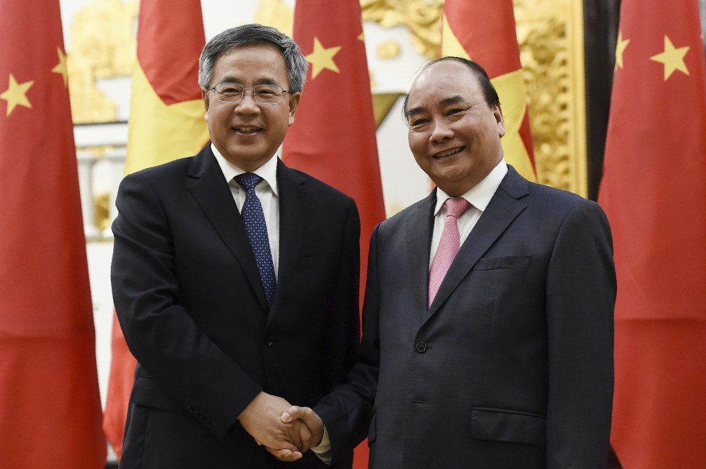 Chinese Vice Premier Hu Chunhua, left, shakes hands with Vietnamese Prime Minister Nguyen Xuan Phuc during their meeting at the Government Office Tues