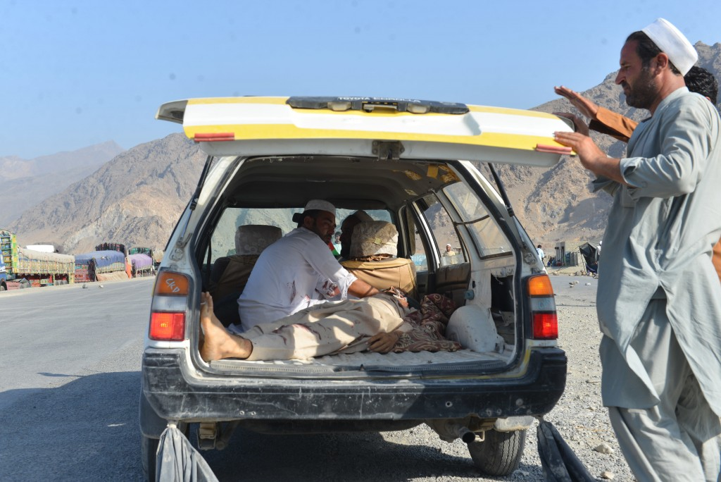 Men carry a dead body with a civilian vehicle in Momandara district of Nangarhar province, Afghanistan, Tuesday, Sept. 11, 2018. A suicide bomber deto