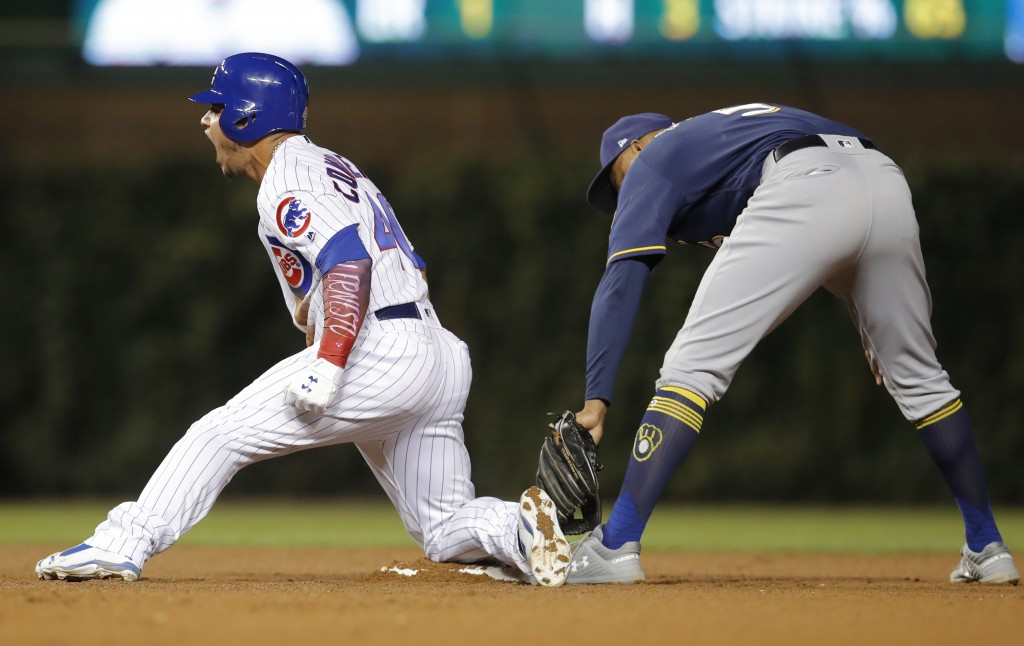 Chicago Cubs' Willson Contreras, left, reacts after sliding into second base safely with a double ahead of a tag from Milwaukee Brewers' Jonathan Scho