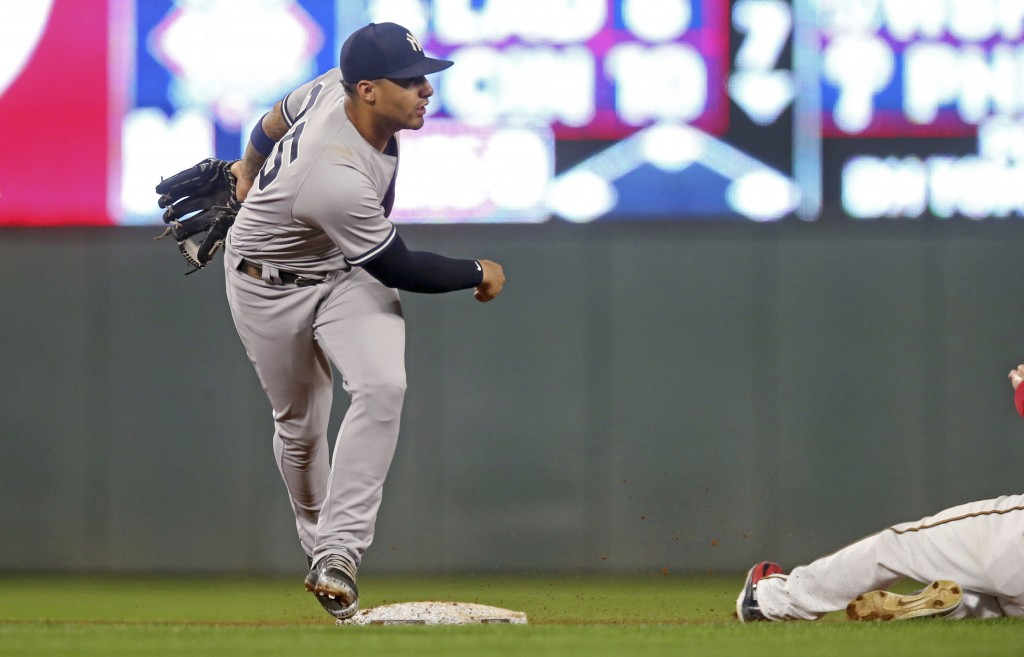 New York Yankees second baseman Gleyber Torres, left, watches his successful throw to complete the double play after the force at second base of Minne