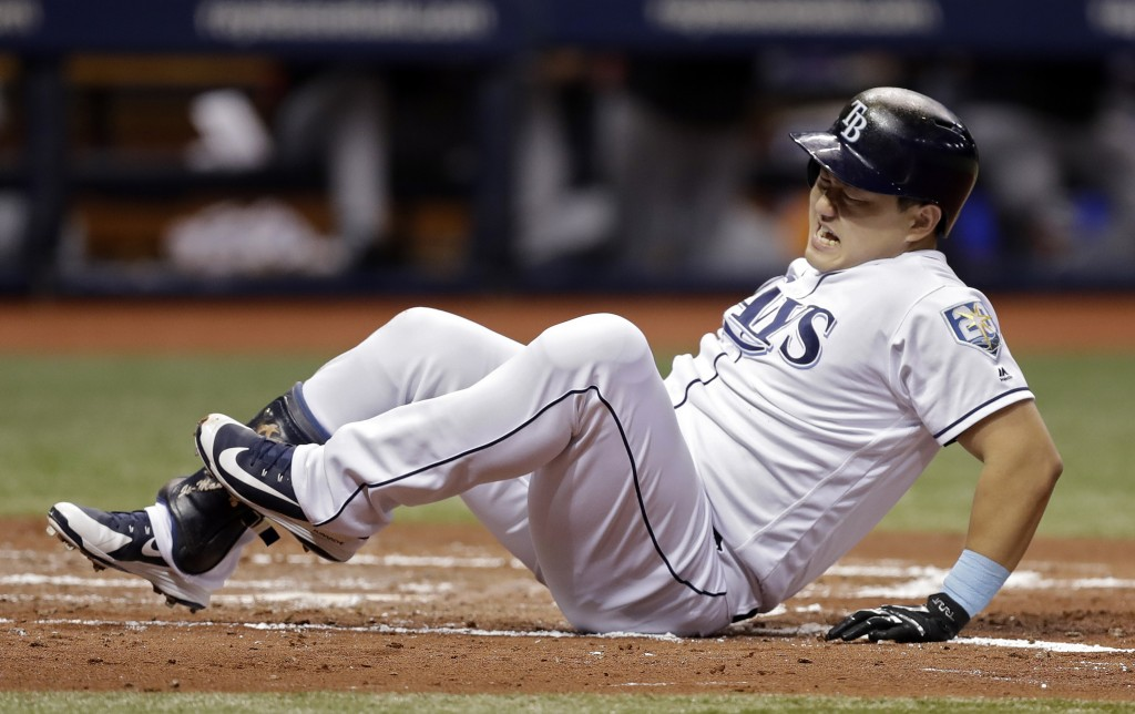 Tampa Bay Rays' Ji-Man Choi, of South Korea, goes down after being hit by a pitch from Cleveland Indians pitcher Corey Kluber with the bases loaded du