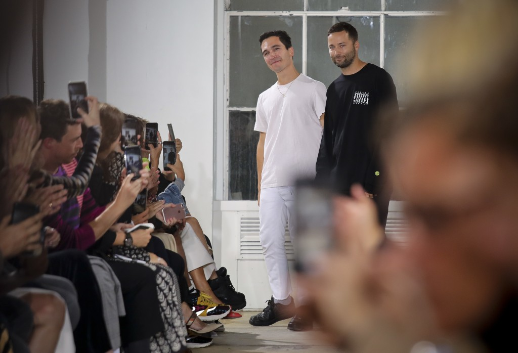 Fashion designers Lazaro Hernandez, left, and Jack McCollough, right, acknowledge applause after unveiling their latest collection for Proenza Schoule
