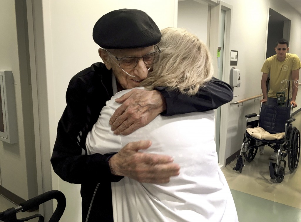 The Rev. John Sabbagh, left, and his son Ebby Sabbagh hugs nurse practitioner Kim O'Riley, Friday, Sept. 7, 2018 in Gilbert, Ariz. Thirty-five years a