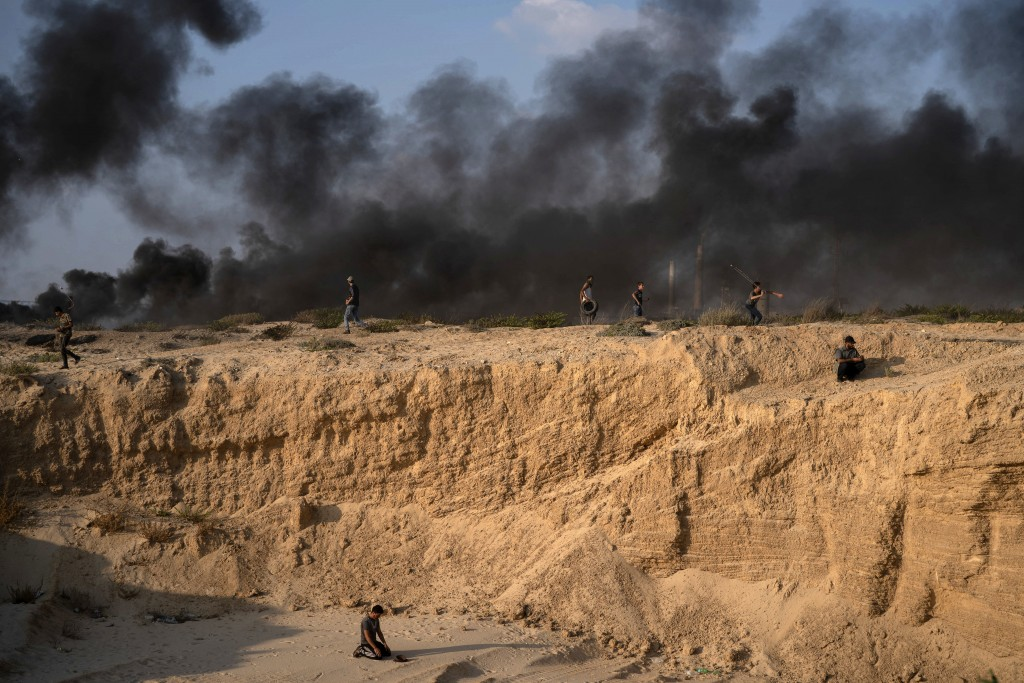 A Palestinian protester prays as others hurl stones and burn tires during a protest on the beach near the border with Israel in Beit Lahiya, northern