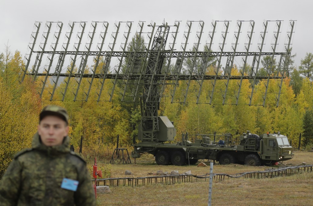 """A Russian soldier stands in front of a Nebo-M radar deployed in a forest, during a military exercises on training ground """"Telemba"""", about 80 kilometer"""