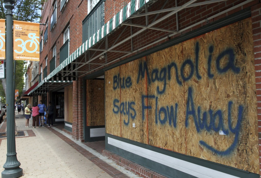 Storefronts have wood paneling installed over windows, Tuesday, Sept. 11, 2018, in New Bern, N.C., as a  precaution against storm damage from Hurrican