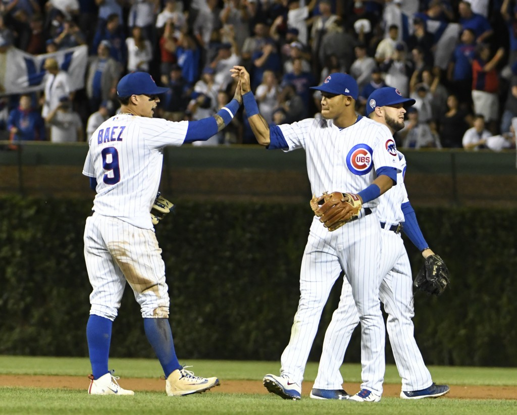 Chicago Cubs second baseman Javier Baez (9) and shortstop Addison Russell (27) celebrate their 3-0 win against the Milwaukee Brewers in a baseball gam