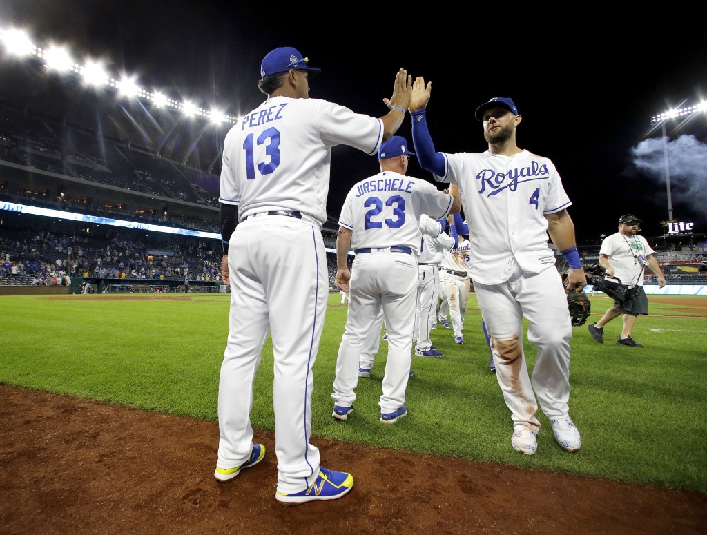 Kansas City Royals' Alex Gordon (4) celebrates with Salvador Perez (13) after their baseball game against the Chicago White Sox Tuesday, Sept. 11, 201