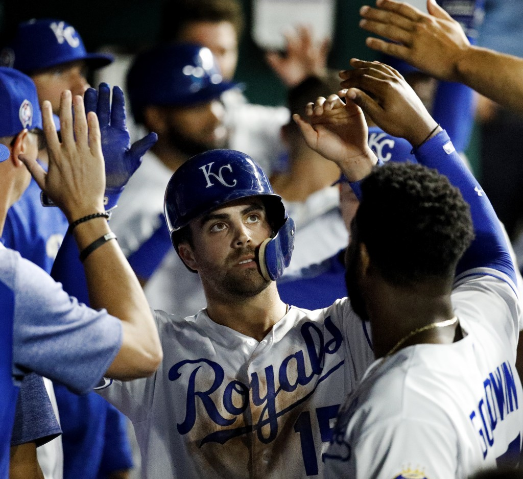 Kansas City Royals' Whit Merrifield celebrates in the dugout after scoring on a sacrifice fly hit by Alex Gordon during the third inning of a baseball