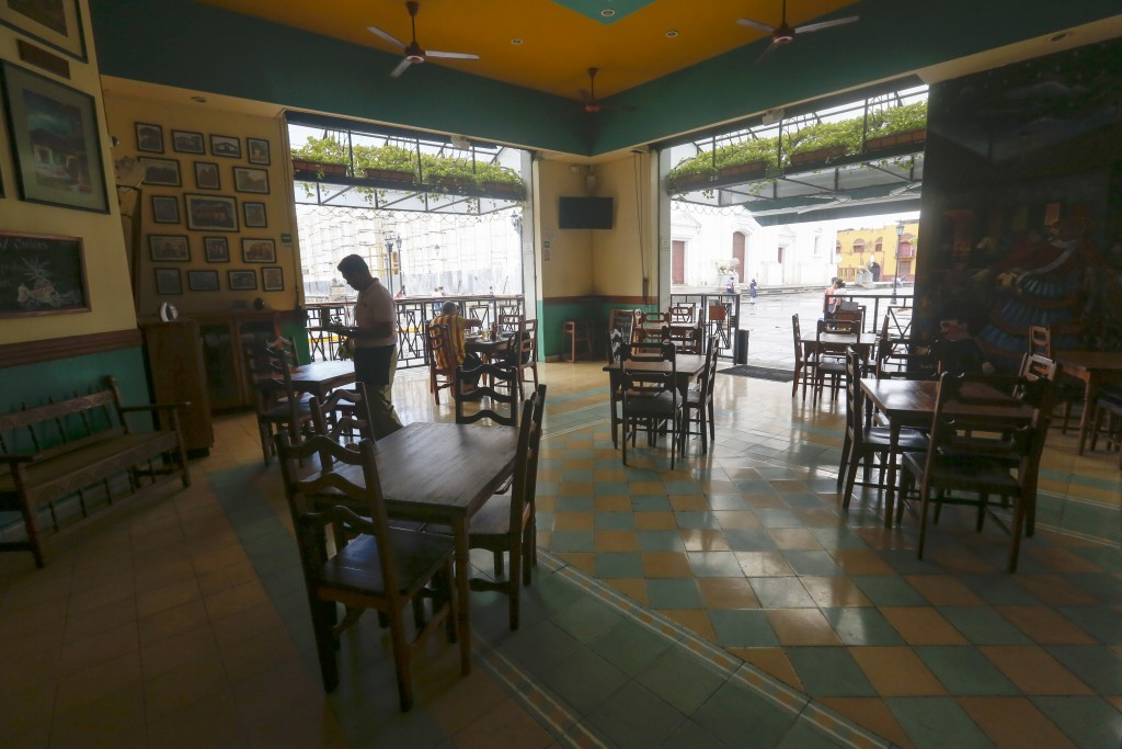 A waiter walks among the empty table of a café in down town Leon, Nicaragua, Tuesday, Sept. 11, 2018. Nicaragua's economy has been devastated by the n