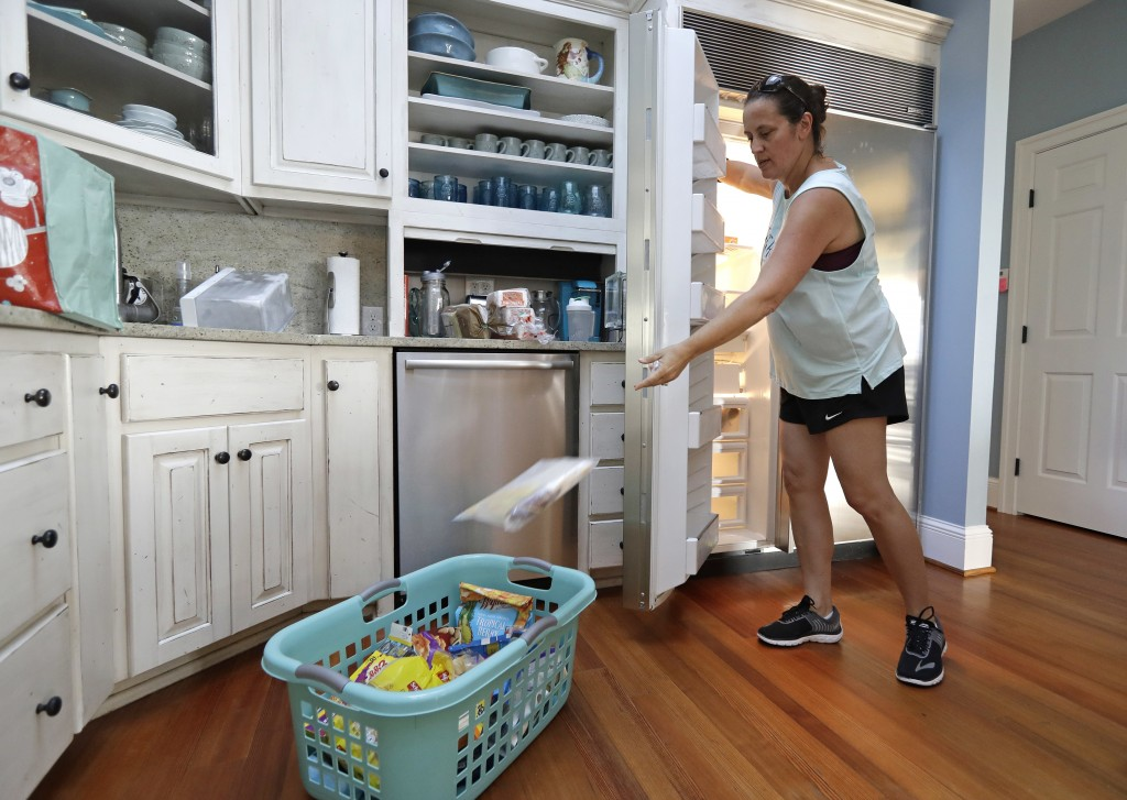 Michelle Stober, of Cary, N.C., removes food from a freezer as she prepares their vacation home in advance of Hurricane Florence in Wrightsville Beach