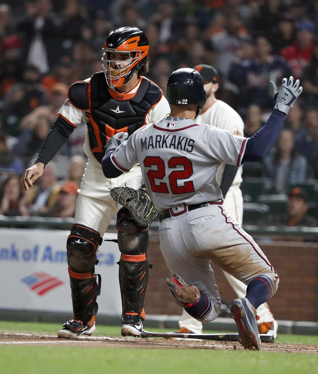 Atlanta Braves' Nick Markakis (22) slides into home plate past San Francisco Giants catcher Aramis Garcia, left, on a sacrifice fly Ender Inciarte dur