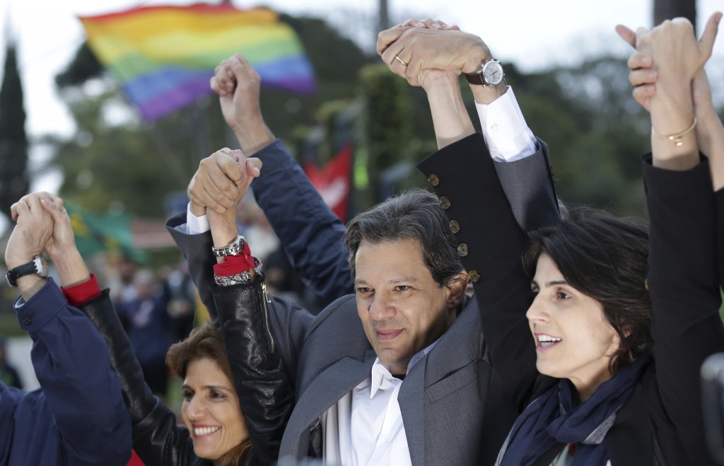 Workers' Party presidential candidate Fernando Haddad, center, and his running-mate Manuela d'Avila, right, hold a campaign rally outside federal poli