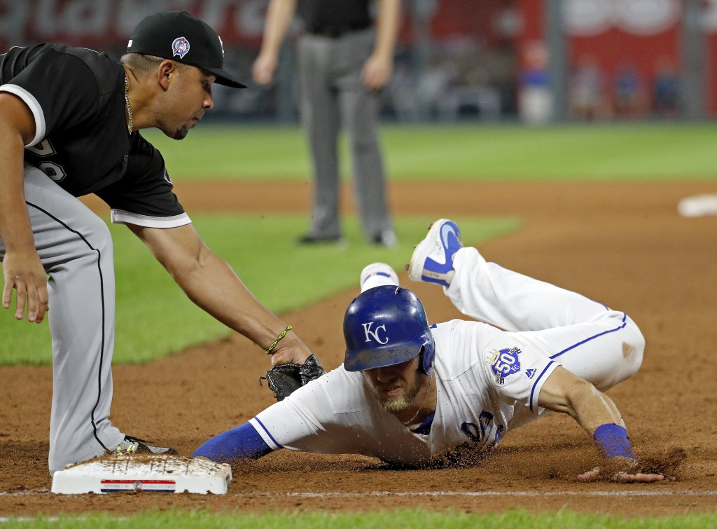 Kansas City Royals' Hunter Dozier is tagged out by Chicago White Sox first baseman Jose Abreu when he dove back to first after getting caught off base
