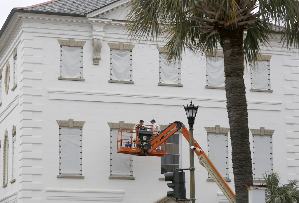 Workers cover the windows of the historic Charleston County Courthouse in Charleston, S.C., in preparation for the advancing Hurricane Florence Tuesda