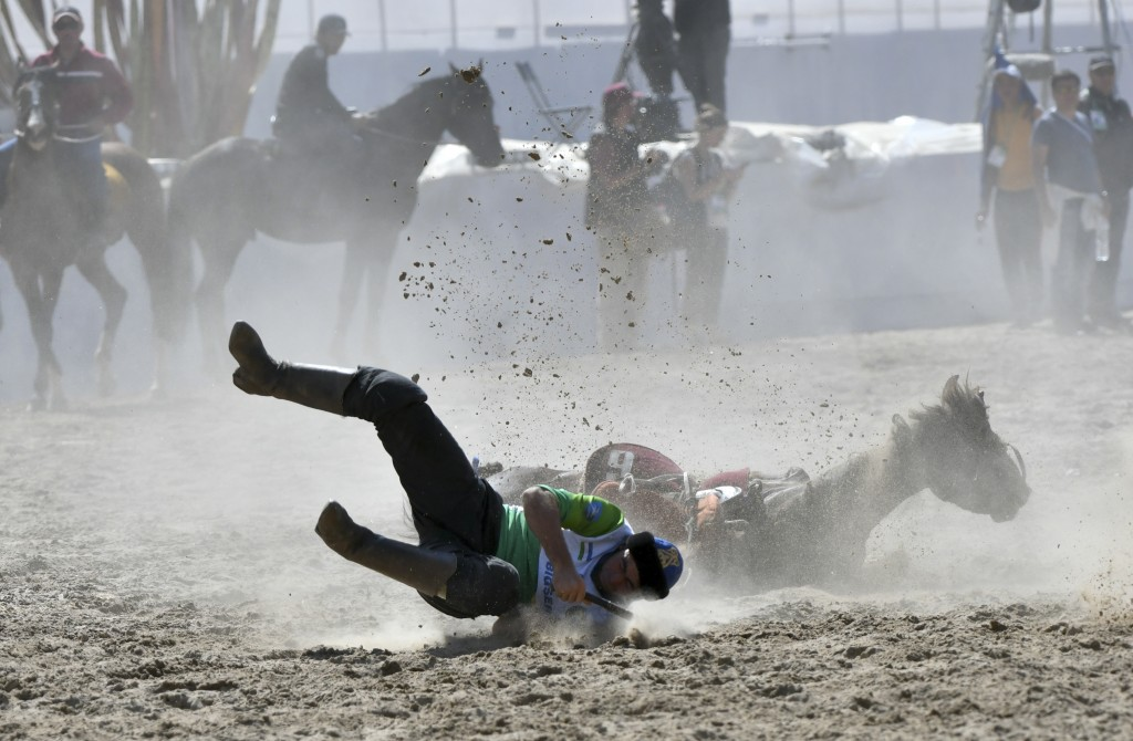 In this photo taken on Wednesday, Sept. 5, 2018, a Kazakh horse rider falls down while competing for the goat during a kok boru, also called ulak tart...
