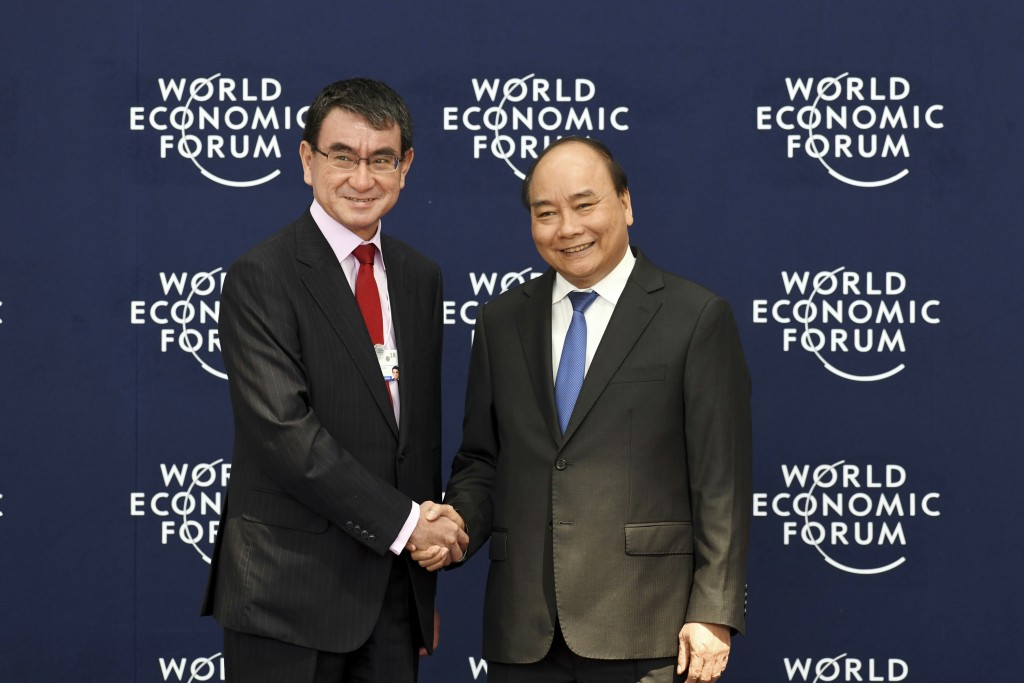 Japan's Foreign Minister Taro Kono, left, shakes hands with Vietnamese Prime Minister Nguyen Xuan Phuc during the welcoming ceremony of the World Econ