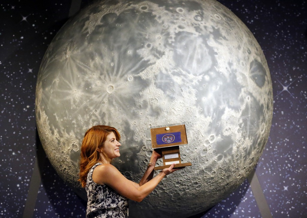 In this Thursday, Aug. 23, 2018, photo, Lindsie Smith, from the Clark Planetarium, holds moon rocks encased in acrylic and mounted on a wooden plaque