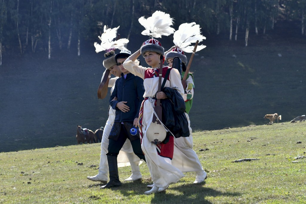 In this photo taken on Saturday, Sept. 1, 2018, participants in traditional Kyrgyz costumes walk during the Third Nomad Games, in Cholpon-Ata, 250 kil